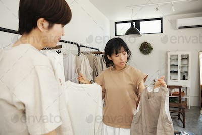 Two Japanese women standing in a small fashion boutique, looking at tops.