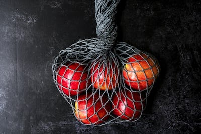 High angle close up of red apples in grey net bag on black background.