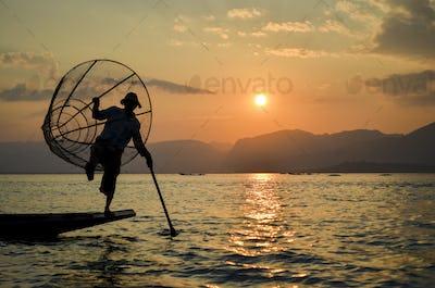 Traditional fisherman balancing on one leg on a boat, holding  fishing basket, fishing on Lake Inle
