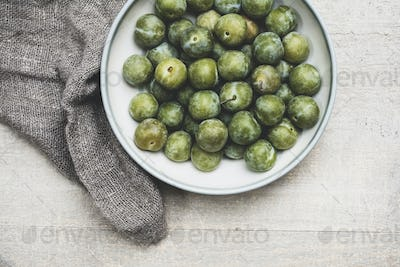 High angle close up of fresh greengages in white bowl.