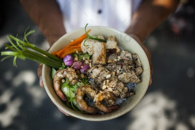 High angle close up of person holding bowl with rice noodles with grilled pork, shrimp, and fish