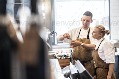 Male and female chef wearing brown aprons standing at a counter, checking an order.