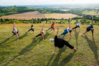 Group of women and men taking part in a yoga class on a hillside.
