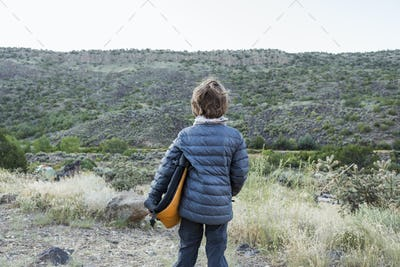 rear view of 6 year old boy holding folded camp chair looking at canyon wall