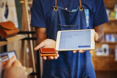 Man wearing blue apron and glasses standing in a leather shop, holding leather purse and digital
