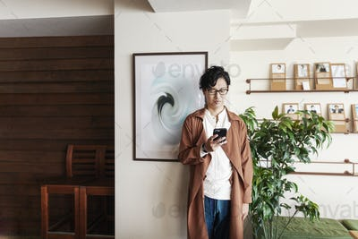 Male Japanese professional standing in a co-working space, looking at his cellphone.
