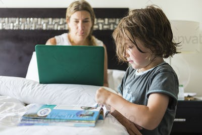 5 year old boy looking at book in hotel room as mom works on laptop