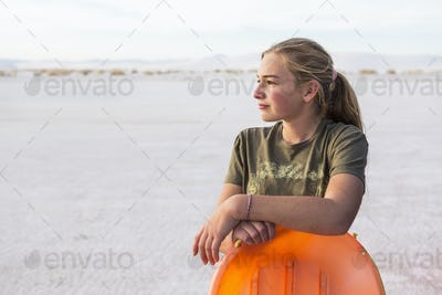portrait of 13 year old girl leaning on orange sled, White Sands Nat'l Monument, NM