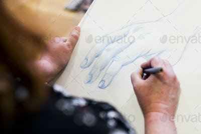 High angle close up of artist drawing human hand.