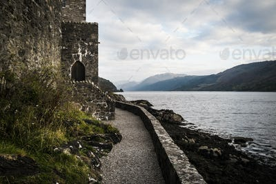 Castle in wall overlooking a loch with mountains in the distance.