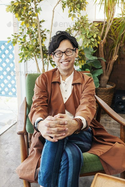 Male Japanese professional sitting in a co-working space, smiling at camera.