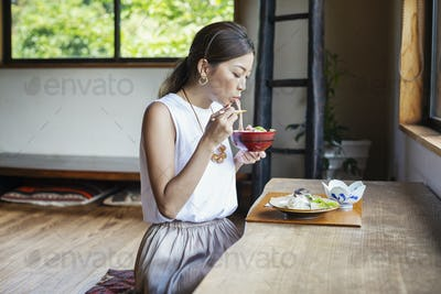 Japanese woman sitting at a table in a Japanese restaurant, eating.