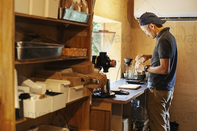 Japanese man wearing baseball cap and glasses standing in an Eco Cafe, preparing cup of coffee.