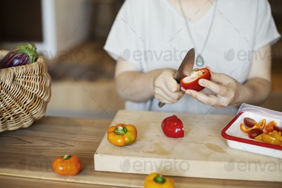 Japanese woman preparing fresh vegetables in a vegetarian cafe.