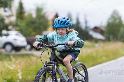 5 year old boy racing his mountain bike on rainy road