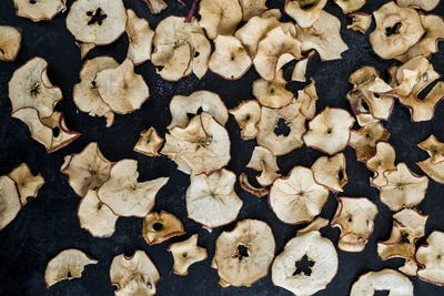 High angle close up of dried slices of apple on dark background.