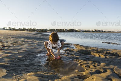 A six year old boy playing on the beach in a pool of water