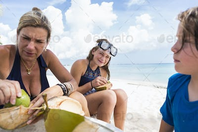 mother and her kids cutting a cocont at the beach