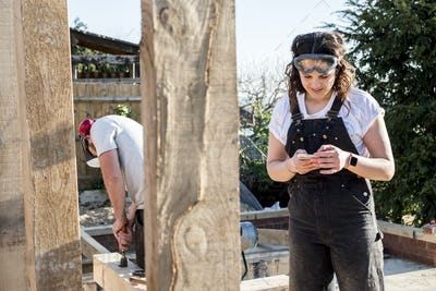 Smiling woman wearing dungarees and protective goggles standing on building site, checking her