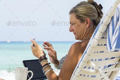 adult woman executive using smart phone on the beach, Grand Cayman Island