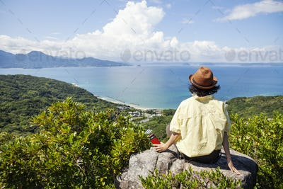 Japanese woman wearing hat sitting on rock on a cliff, ocean in the background.