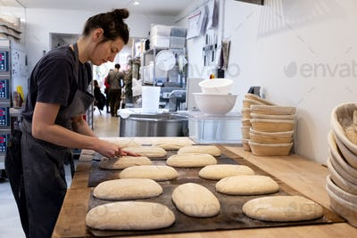 Woman wearing apron standing in an artisan bakery, shaping sourdough loaves for baking.