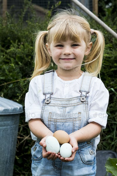 Blond girl standing in a garden, holding fresh eggs, smiling at camera.