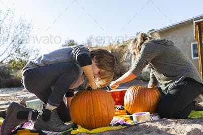 A teenage girl  and her brother carving pumpkins at Halloween.