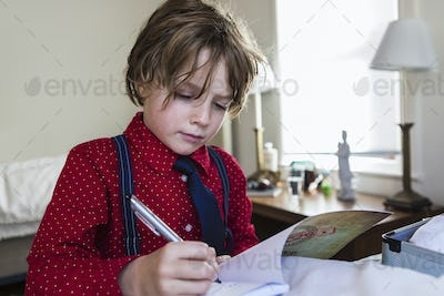 6 year old boy drawing on sketch pad in