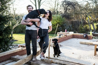 Smiling man and women and two black dogs on building site of residential building.