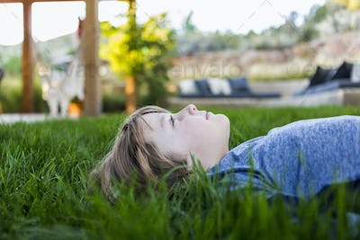 portrait of smiling 6 year old boy lying down in green grass