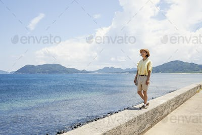 Japanese woman wearing hat standing on a wall, looking at ocean.