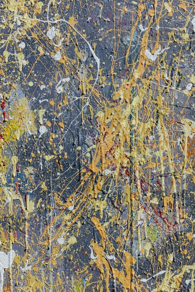 Colorful graffiti paint splattered and dripping on urban wall, close up