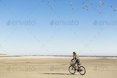 A teenage girl cycling on sand towards a flock of seagulls, St. Simon's Island, Georgia
