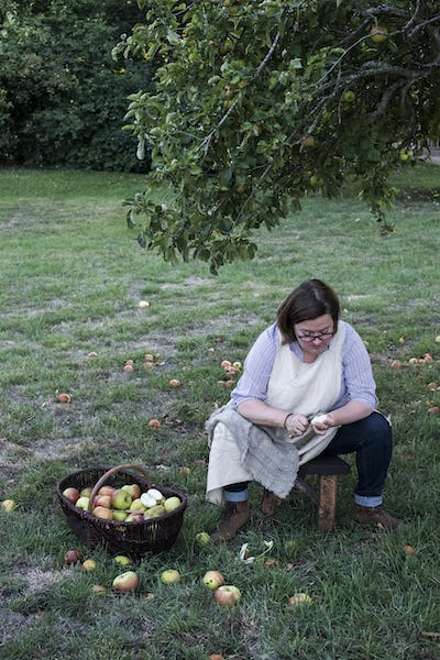 Woman sitting in an orchard under apple tree next to brown wicker basket with freshly picked apples,