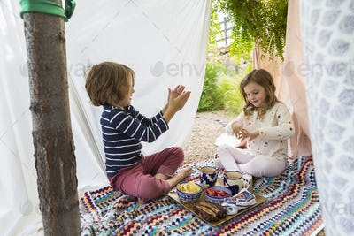 young boy and girl playing in outdoor improvised tent