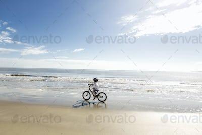 6 year old boy biking on beach, St. Simon's Island, Georgia