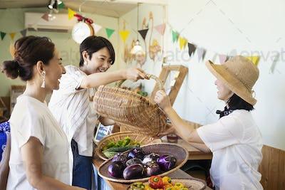 Japanese women shopping fresh vegetables in a farm shop.