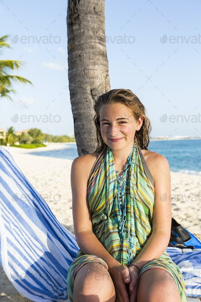 smiling 13 year old girl sitting in beach chair, Grand Cayman Island