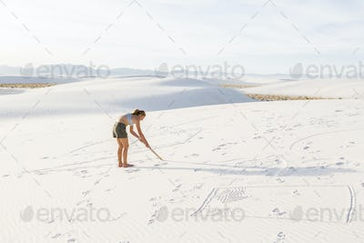 13 year old girl drawing in the sand, White Sands Nat'l Monument, NM