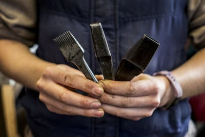 Close up of person holding three metal saddle making tools.