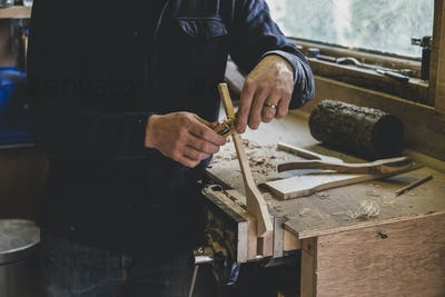 Bearded man wearing black beanie standing at workbench in workshop, working on piece of wood.