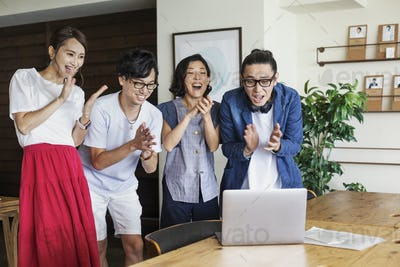 Group of young Japanese professionals looking at laptop computer in a co-working space, smiling and
