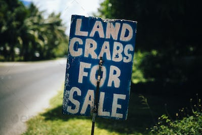 Handwritten sign by the side of road advertising land crabs for sale.