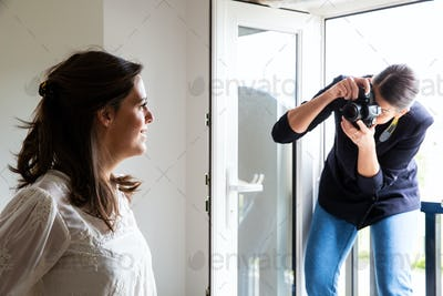A professional make up artist at work, taking photograph of woman.