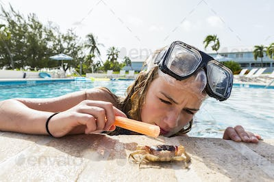 13 year old girl looking at live crab near pool