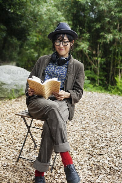 Japanese woman wearing glasses and hat sitting on chair outside Eco Cafe, reading book.