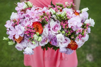 High angle close up of woman holding two bouquets of flowers with pink roses.