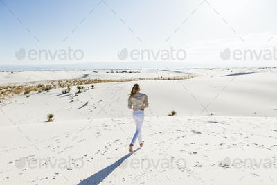 13 year old girl standing looking at a vast open space of sand dunes.