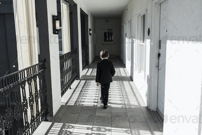 6 year old boy walking down corridor